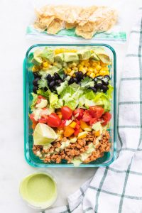 Taco salad meal prep bowls with dressing on top.