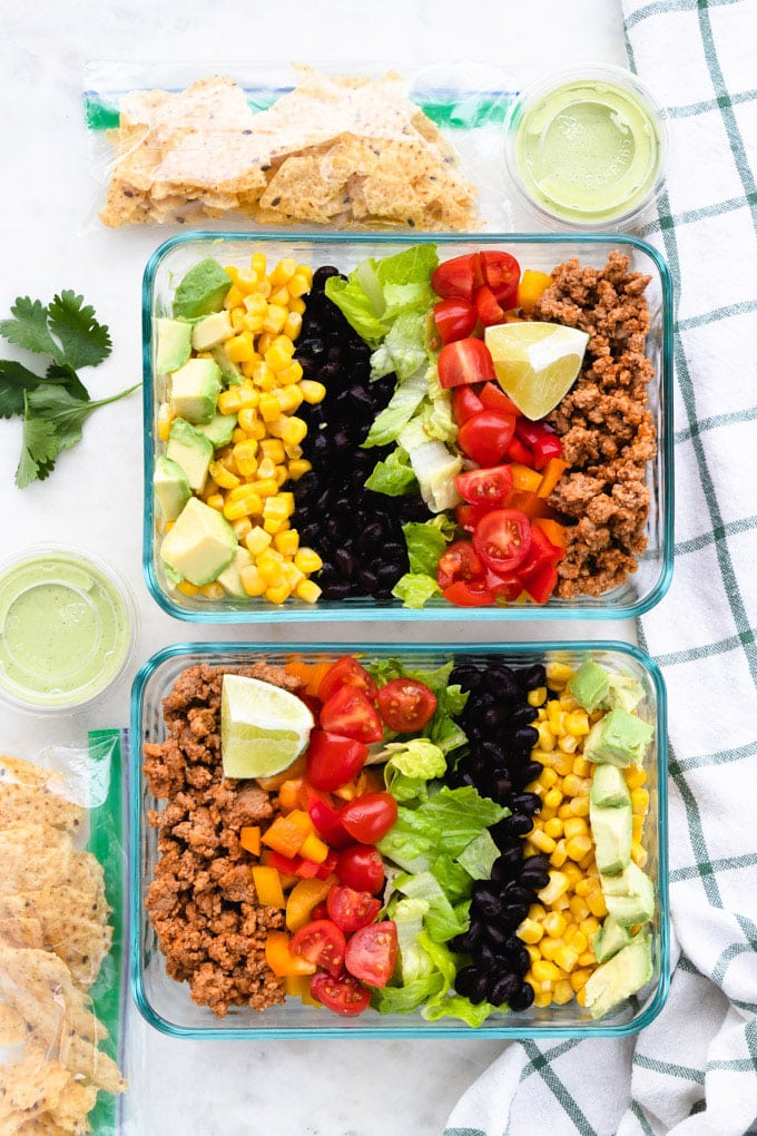 A healthy taco salad with toppings on the side.