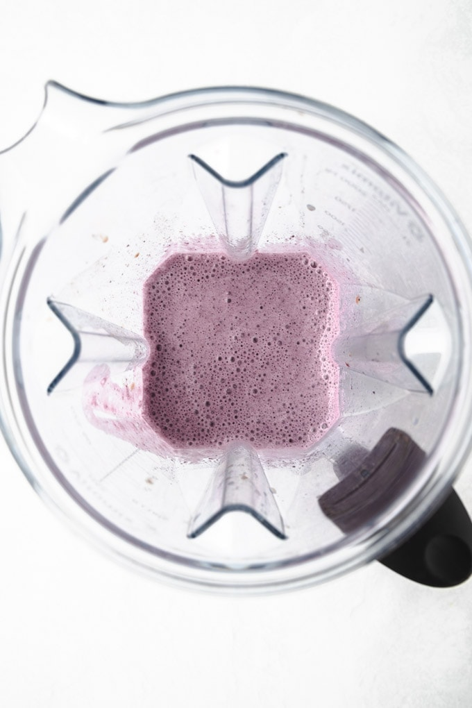 Inside of a blender with a blueberry smoothie in it.