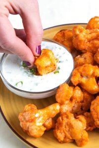 a hand dunking buffalo cauliflower into blue cheese sauce