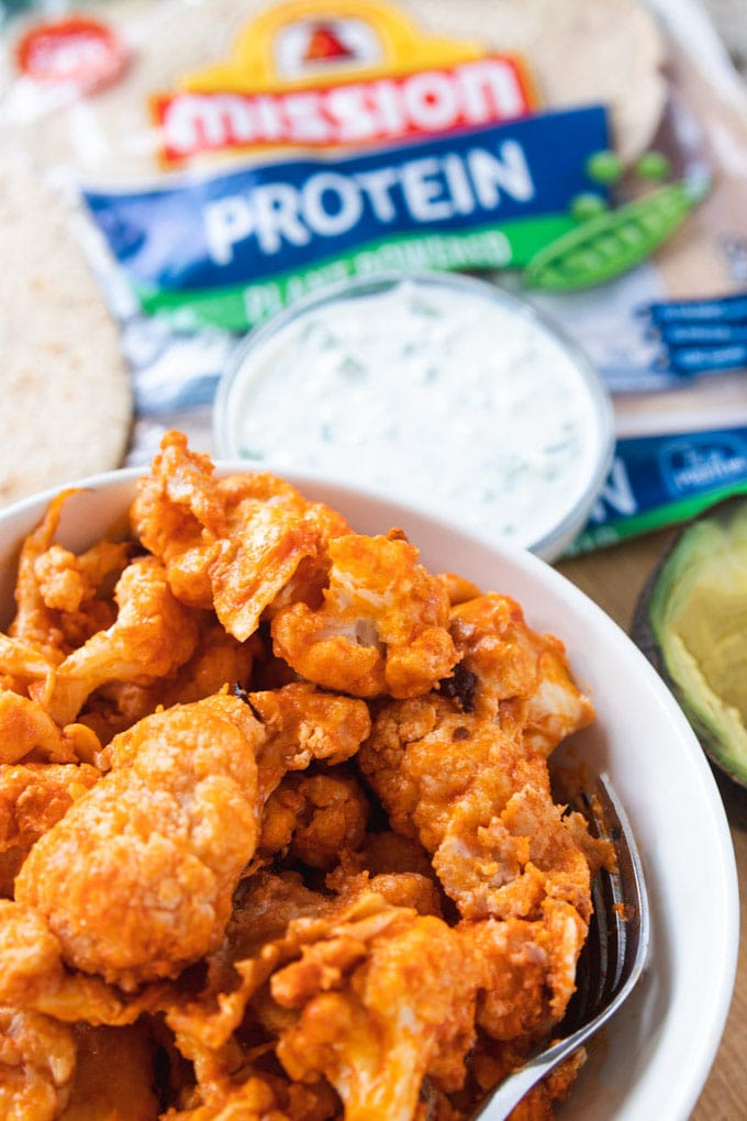 buffalo cauliflower wings in a bowl with sauce.