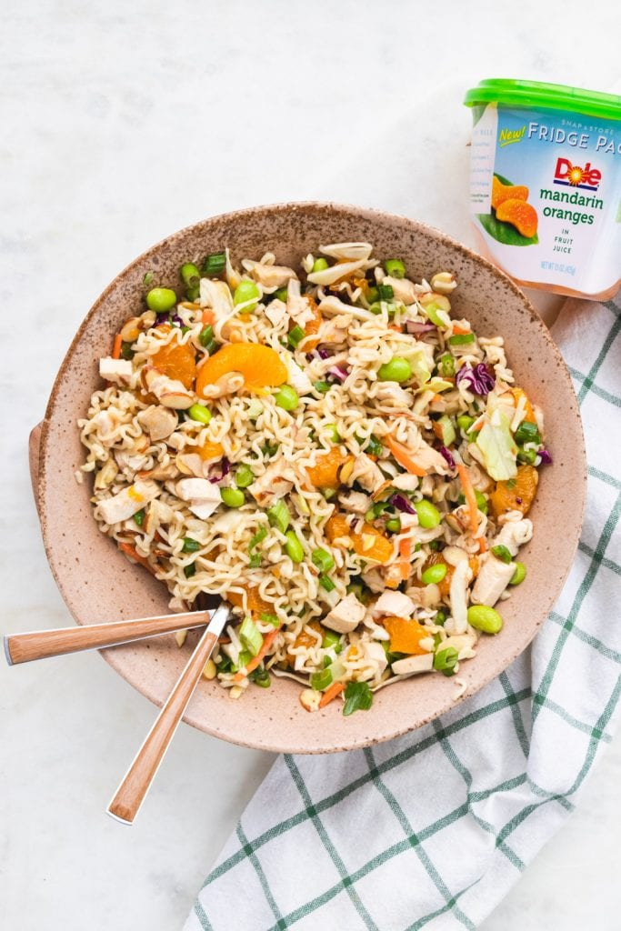 healthy Asian chicken salad in bowl with ramen and mandarin oranges.