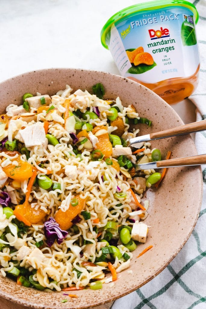 Asian chicken salad in a bowl with oranges and ramen noodles.
