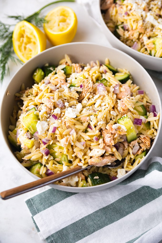 A bowl of salmon orzo salad with lemons behind it.