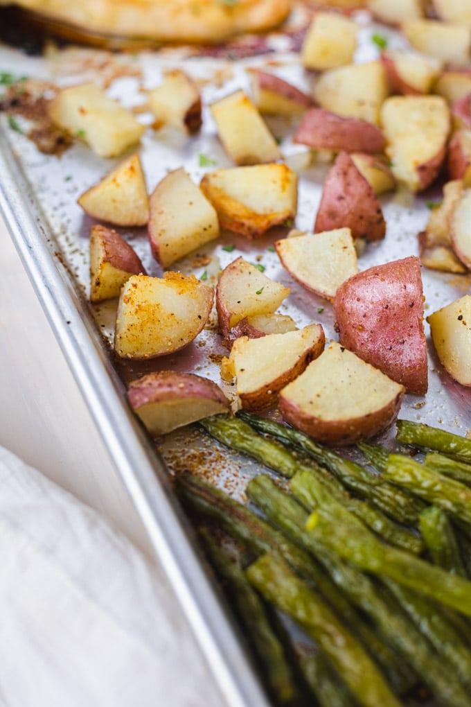 A close up of crispy potatoes on a sheet pan.