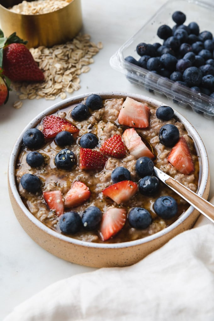 oatmeal with berries and strawberries with a spoon.