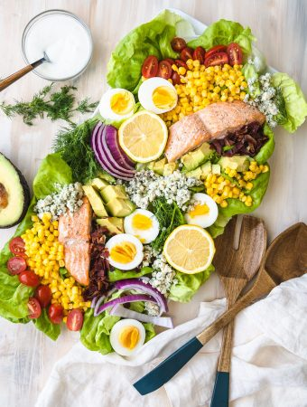 salmon Cobb salad on a plate with wooden serving spoons.