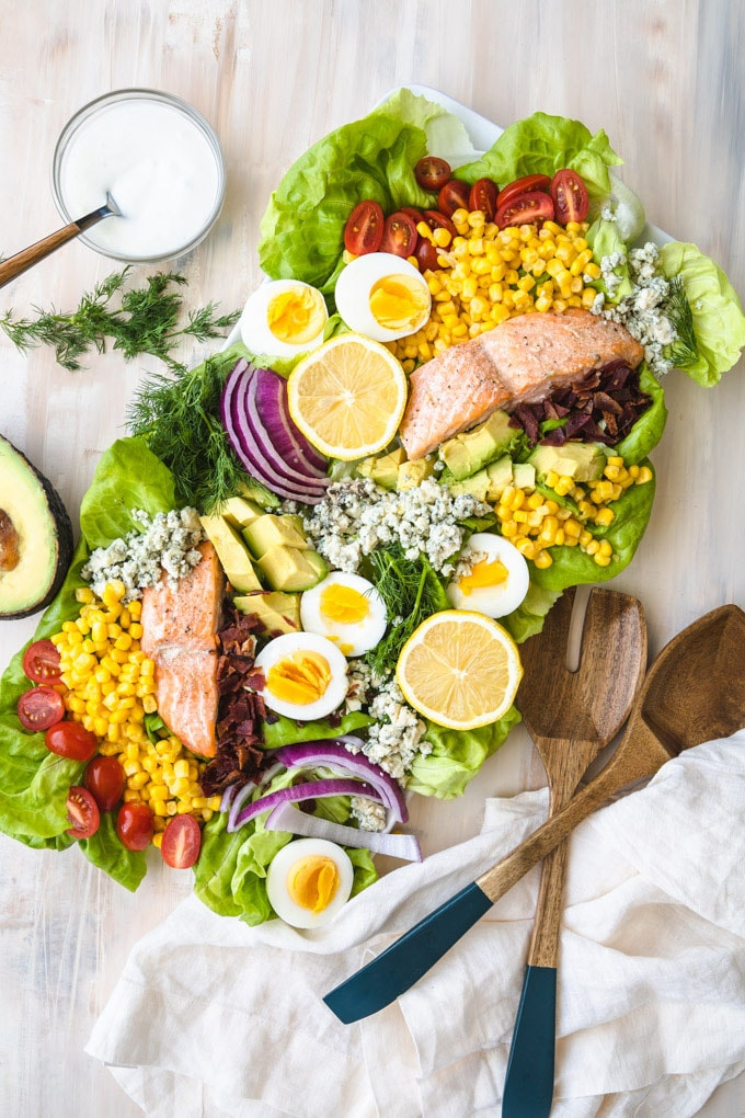 salmon salad recipe on a plate with dressing on the side.