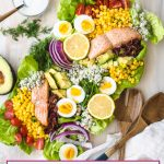Cobb salad on a platter with spoons and dressing