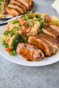 Sauce on chicken with rice and vegetables.