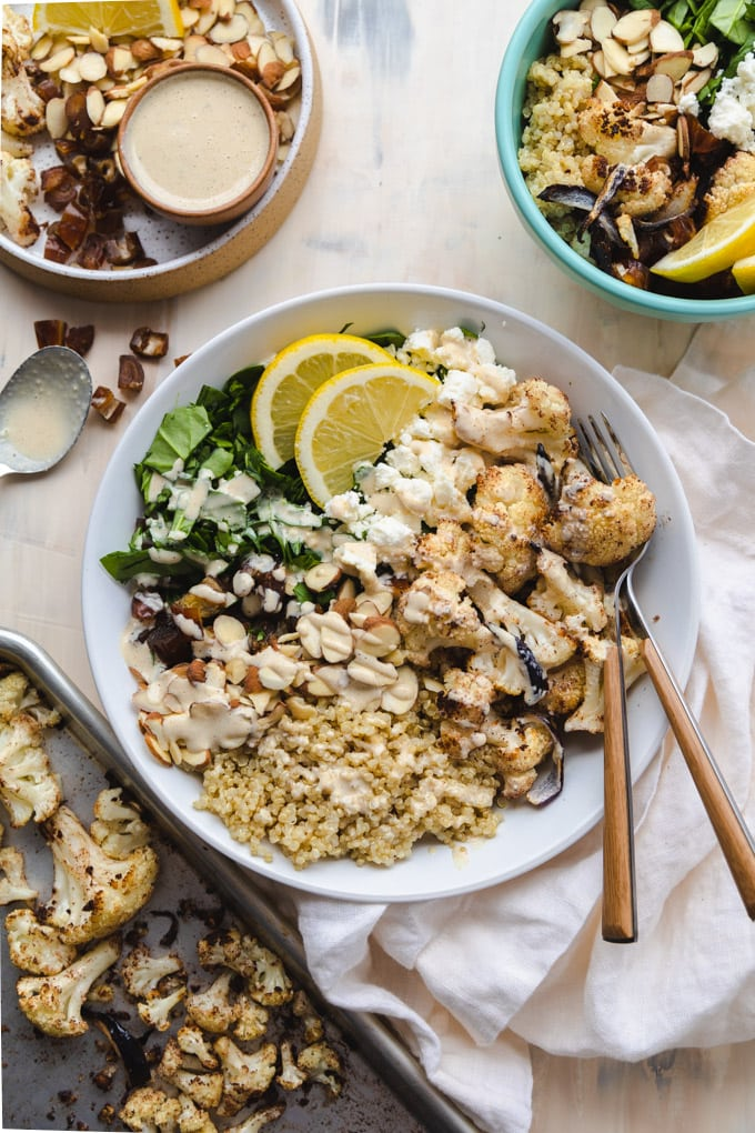 A bowl of healthy mediterranean cauliflower salad with toppings around it.