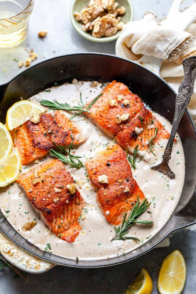 Salmon in a cast iron skillet with lemons.