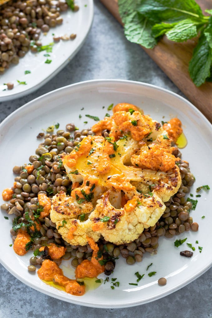 Cauliflower steak over a bed of lentils on a plate.