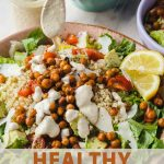 a bowl full of salad with chickpeas, lemon and caesar dressing.