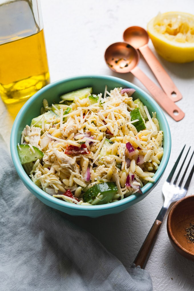 chicken pasta salad in a bowl with toppings around it.