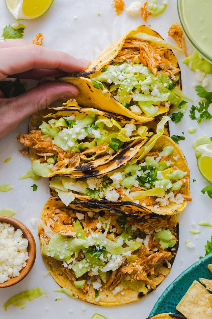 tacos with toppings around them and a hand grabbing one.
