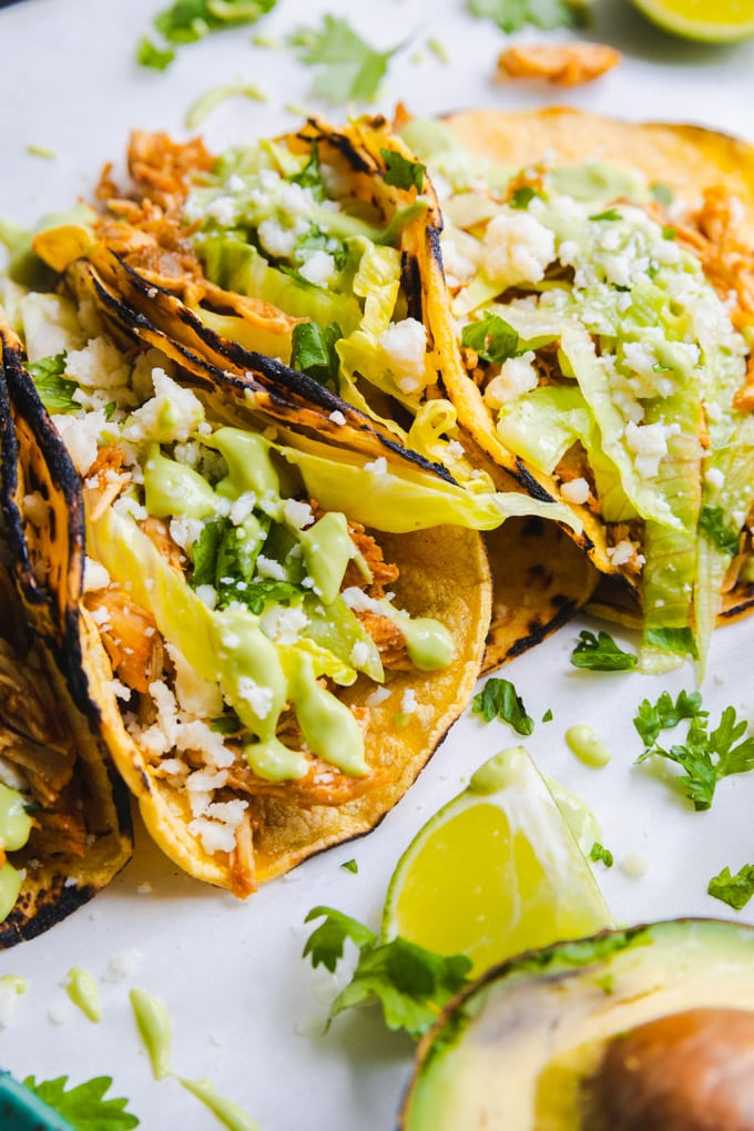 tacos with sauce and chicken and a lime wedge.