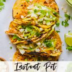 Instant pot chicken tacos in a line with toppings around them