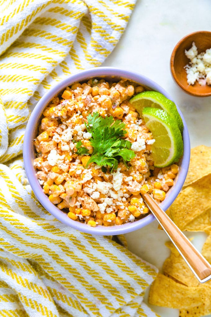 a bowl of elote with lime and chips around it.