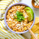 a bowl of Mexican corn dip with lime and cilantro