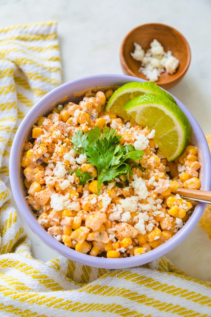 Mexican corn dip with limes and cheese in a bowl.