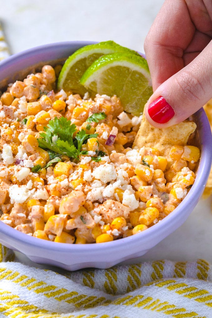 a hand dipping a tortilla chip into a bowl of Mexican street corn dip.
