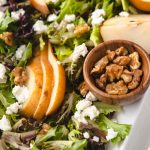 candied walnuts in a small bowl in a salad of goat cheese and lettuce.