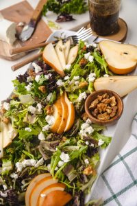 Pear and goat cheese Salad on a plate with toppings around it.