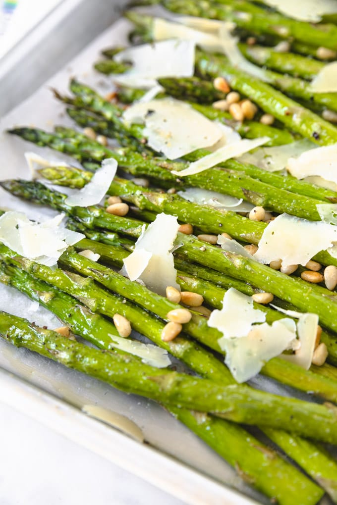 asparagus with pine nuts and parmesan on a serving tray