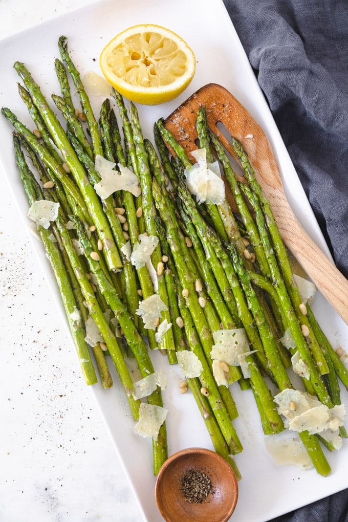 Black pepper and asparagus on a serving tray with a spatula.