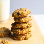 a stack of oatmeal cookies with a glass of milk.