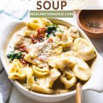 Chicken tortellini soup in a bowl with cheese on top.
