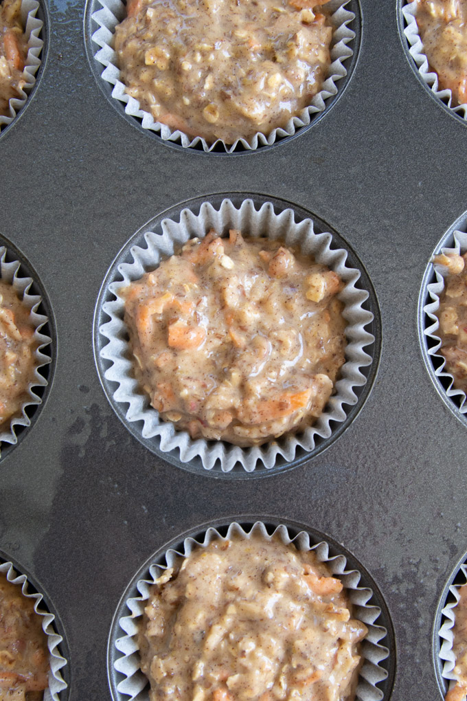 Muffin liners filled with breakfast muffin batter.