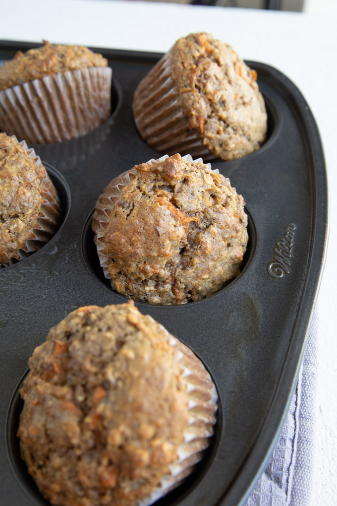multiple muffins popping out of the muffin tin with liners.