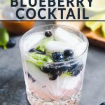 a glass filled with ice cubes, blueberries and basil.
