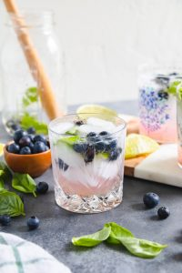 basil blueberry cocktail in a glass with ice cubes and blueberries around it.