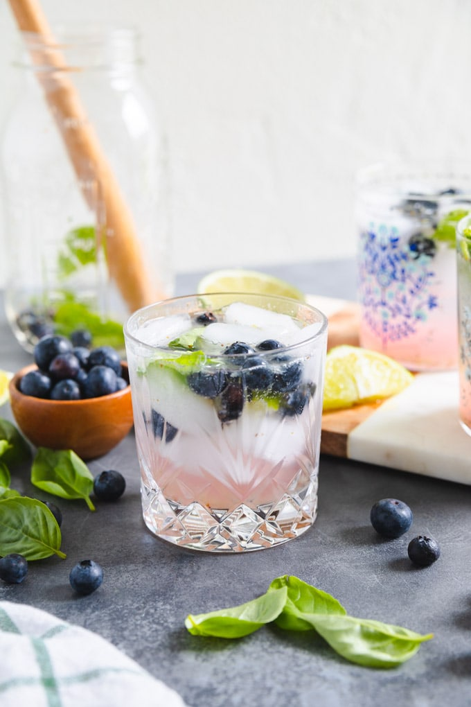 A glass full of basil and blueberries with lime.