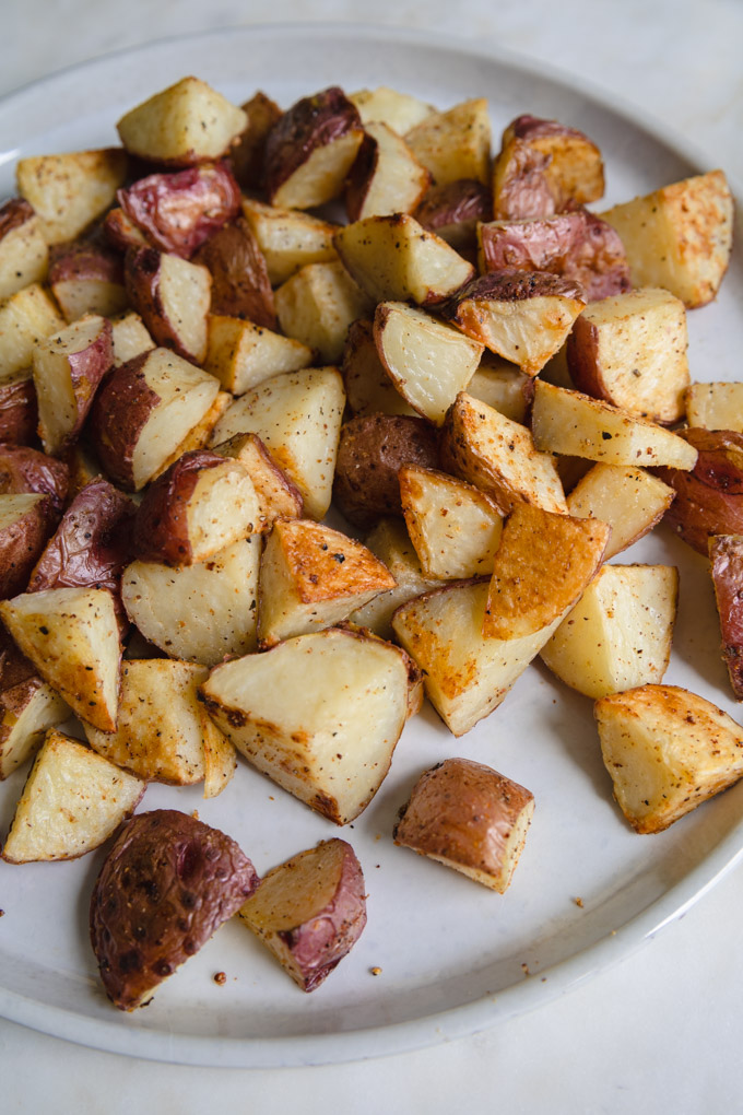 unseasoned roasted red skin potatoes on a plate.