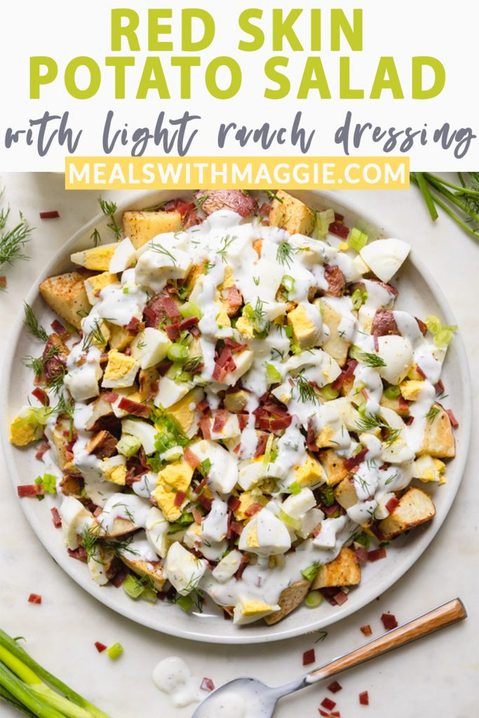 potato salad with toppings on a plate with dressing drizzled over top and a spoon.