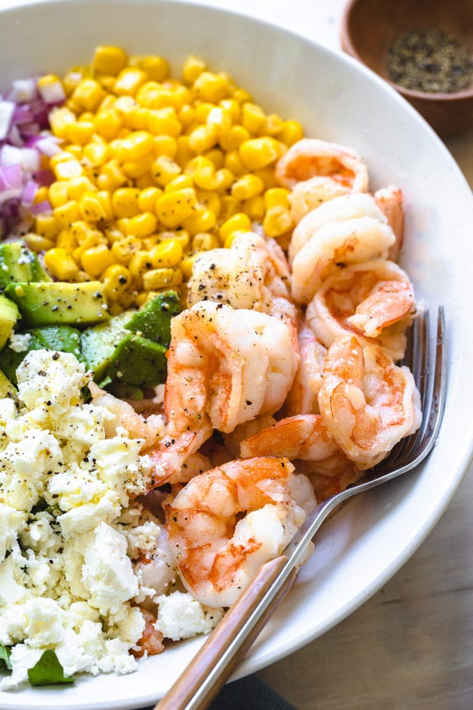 shrimp and feta in a bowl with a fork and other vegetables.
