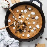 cast iron skillet with marshmallows and chocolate around it.
