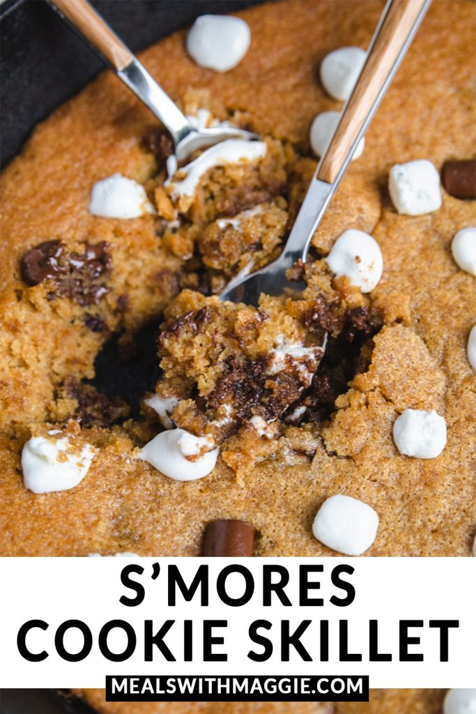 Two spoons in the s'mores cookie skillet with melted chocolate and marshmallows.
