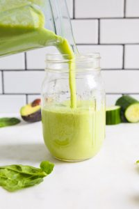 a mason jar being poured with a green smoothie.