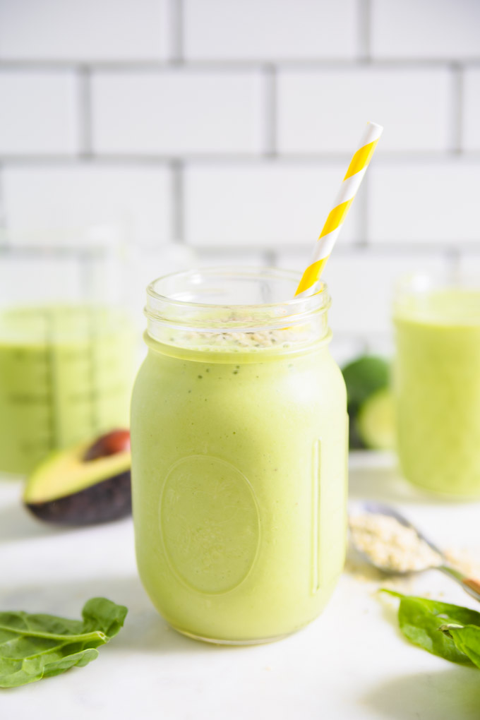 green smoothie in a mason jar with a straw and an avocado next to it.