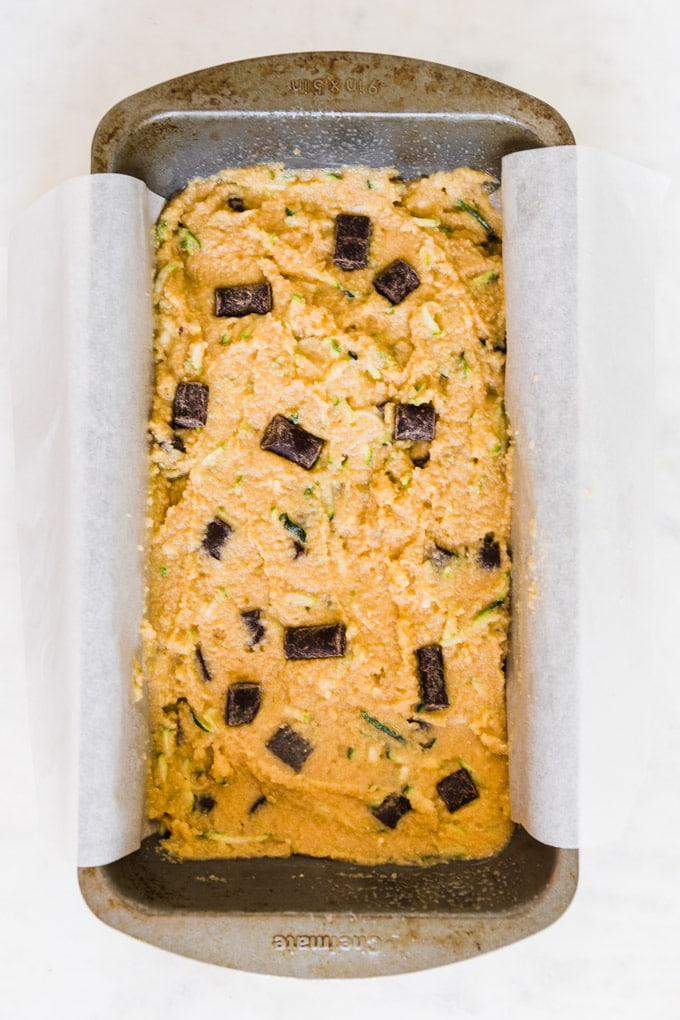 zucchini bread batter in a loaf pan with parchment paper.