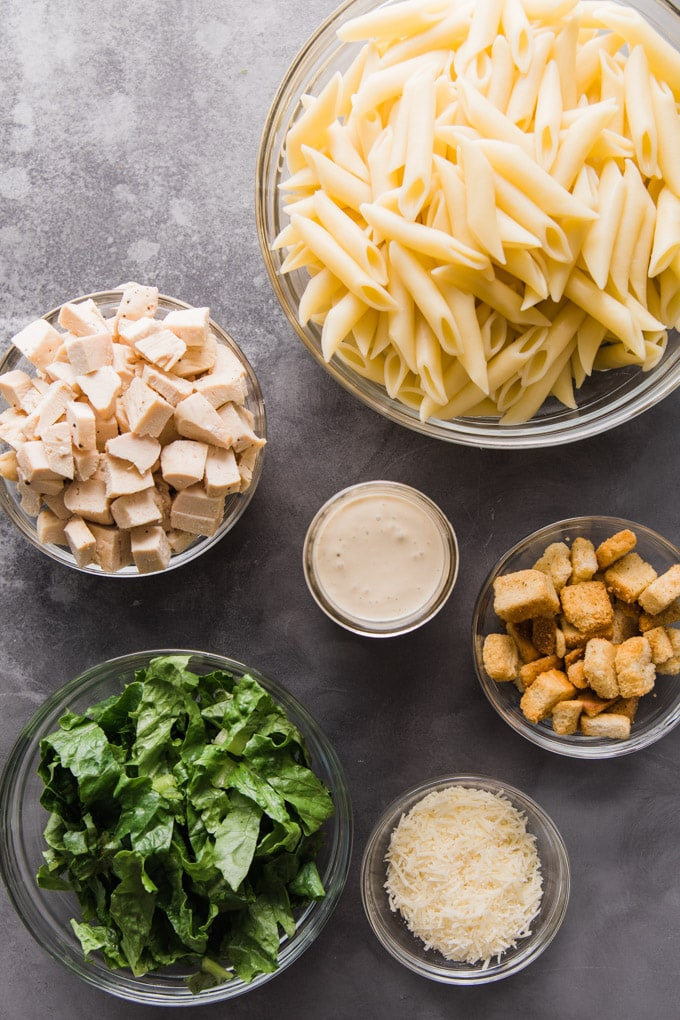 Ingredients for chicken caesar pasta salad in bowls.