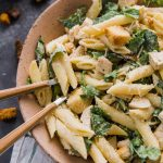 chicken caesar pasta salad in a bowl with forks.