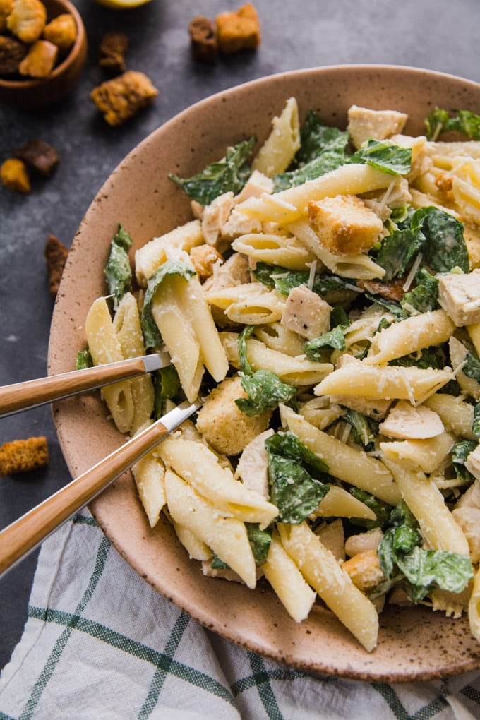 A bowl of chicken caesar pasta salad with two forks in it.
