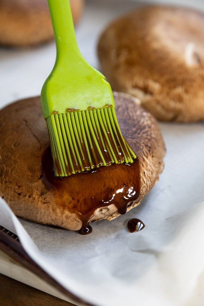 A brush with sauce brushing a portobello mushroom cap.