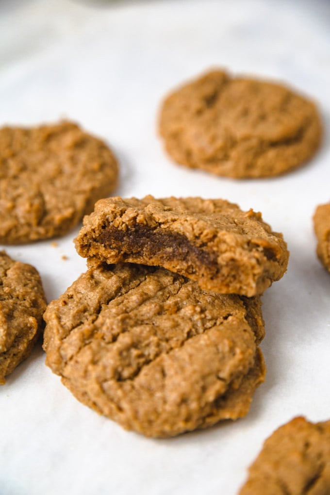 a peanut butter cookie on a sheet pan with a bite taken out of it.